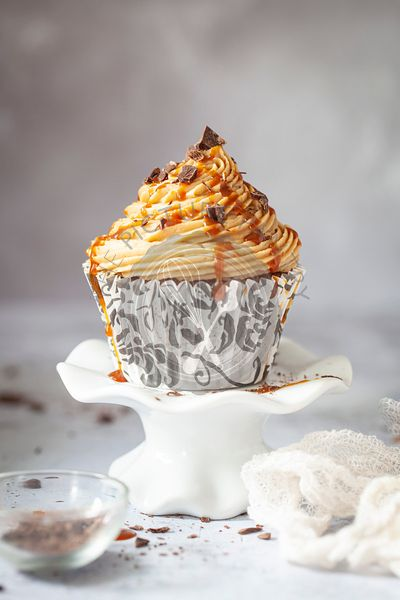 A caramel and coffee cupcake on a cakestand. The cake is topped with coffee buttercream, caramel sauce and chocolate