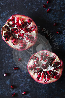 Two pomegranate halves on a dark blue background.