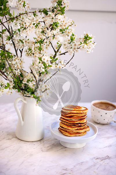 Stack of pancakes on a small white cake stand
