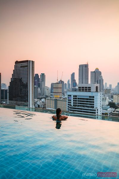 Woman in an infinity pool looking at Bangkok skyline