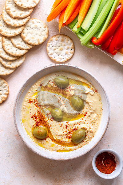 Red lentil hummus with sliced vegetables and crackers on the table.