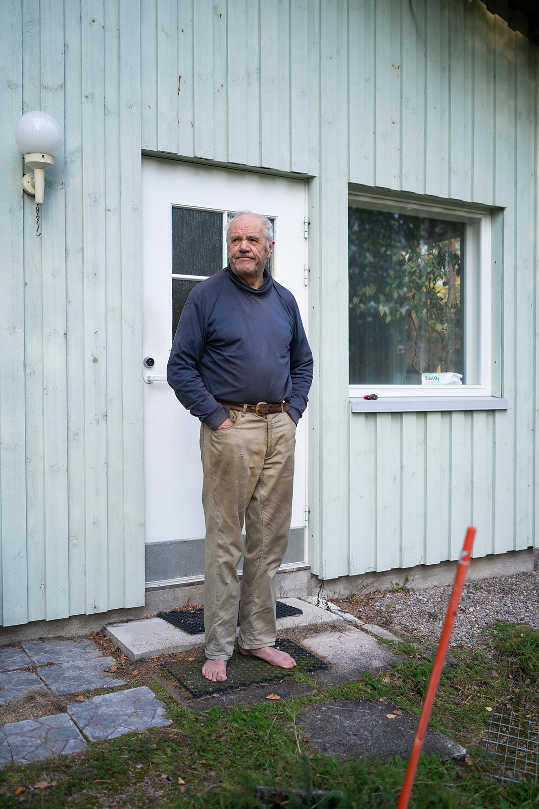 Pensioner Olavi Toivola in front of his sel-designed and built home in Petäjävesi.