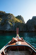 Woman suntanning on boat prow, Phi Phi island, Thailand