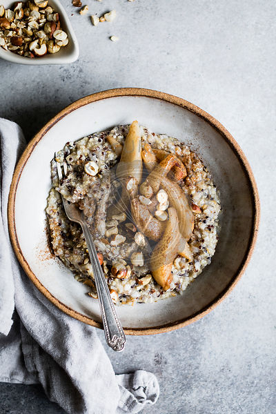 A healthy multigrain porridge with a topping of warm spiced pears and hazelnuts for a hearty breakfast.