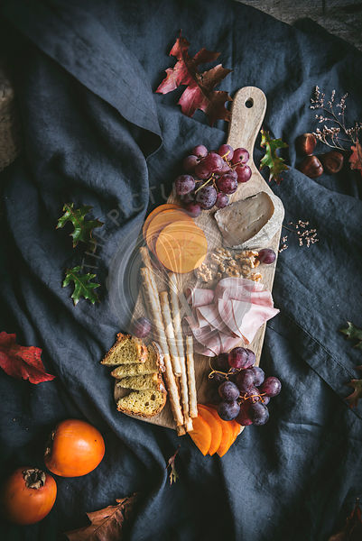 A cheese board with grapes, bread sticks, sharron fruit, persimmons.