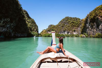 Young woman in swimwear sitting on boat prow, Krabi, Thailand