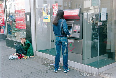 Beggar sitting near cashpoint to shame people into donating.