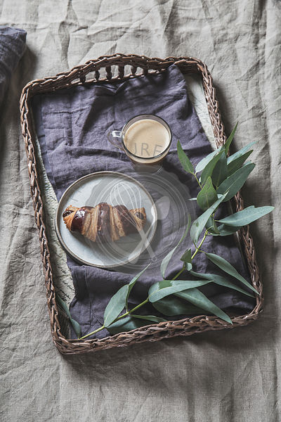 Wicker tray with coffee and croissant on a linen bed. Breakfast in bed