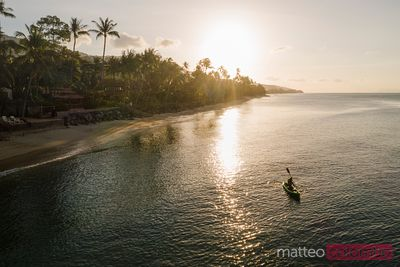 Aerial view of woman kayaking at sunset, Thailand