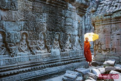 Monk with umbrella walking inside a temple, Angkor