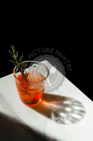 Negroni cocktail with a rough ice cube and a rosemary sprig garnish on the corner of a marble table with the shadow featuring.