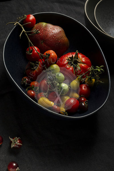 A selection of various heirloom tomatoes in a large, dark blue free form bowl. There is a stack of grey dishes in the backgro...