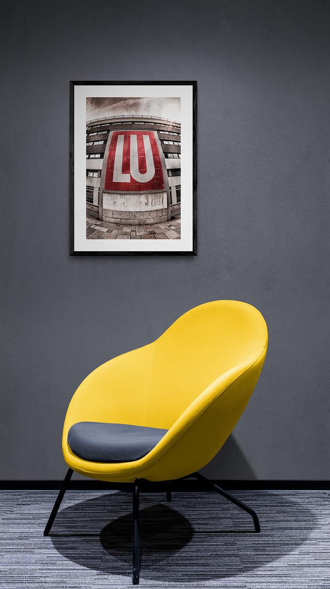LU_Nantes_Trendy_fabric_chair_next_to_spotlit_wall