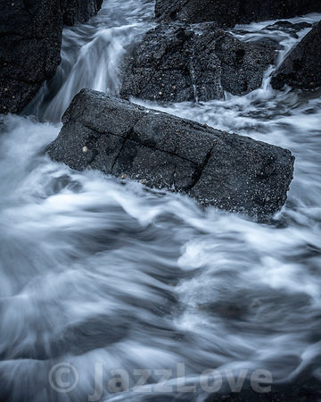 Wave splashing on dark, wet rocks.