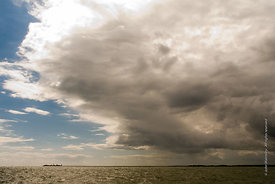 #061934,  Gathering cumulus storm clouds at sea.