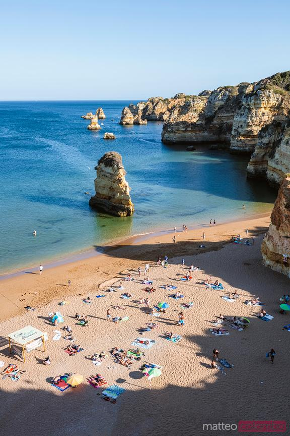 Dona Ana beach at sunset with people, Portugal