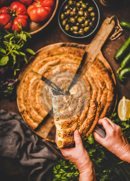 Human hands holding piece of Turkish borek pie with spinach