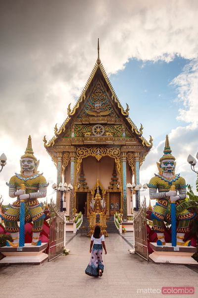 Woman walking to famous Wat Plai Laem, Ko Samui, Thailand