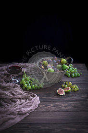 Fresh figs and grapes in a bucket and on rustic wooden table
