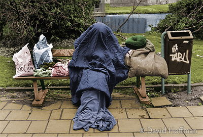 Unrecognisable homeless person with head covered by a sleeping bag sitting on a bench.