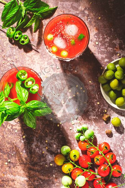 2 glasses of Bloody Mary garnished with basil leaves and jalapeño, with olives and red and green tomatoes placed aroud.