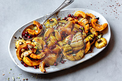 Roasted delicata squash with pomegranate and pistachios on a plate.