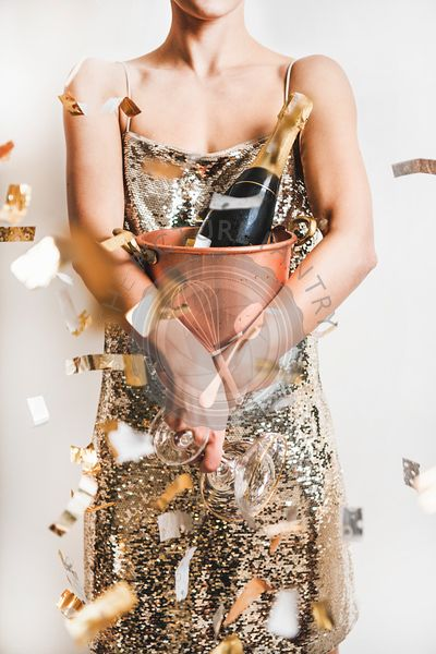 Woman in golden dress holding bucket with champagne in confetti