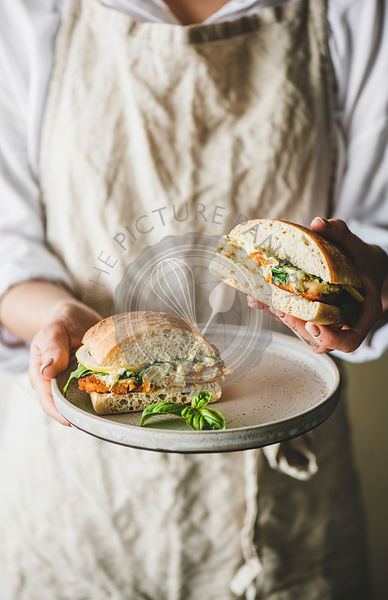 Woman holding fresh breakfast sandwich with fried fish, lemon, arugula