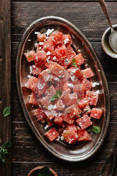 Watermelon salad with feta and mint on a wooden backdrop