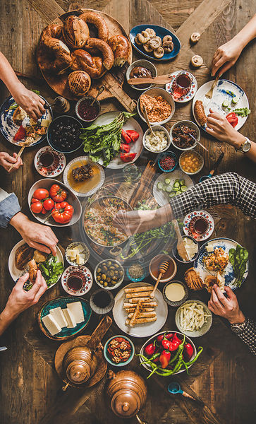 Flat-lay of peoples hands holding traditional turkish breakfast cuisine food