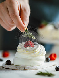 Female hand decorates mini Pavlova cake with rosemary