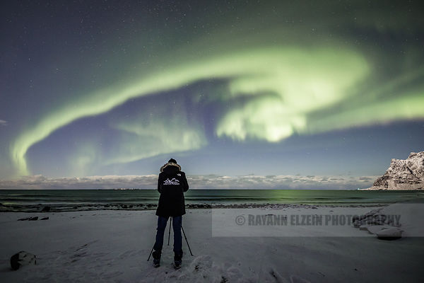 Photographer adjusting his shot of the nothern lights (Aurora Borealis) on the Uttakleiv Beach in Lofoten, Norway