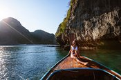 Woman on longtail boat prow, Maya bay, Phi Phi island, Thailand
