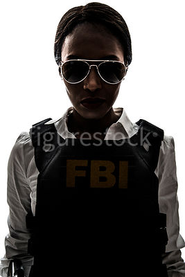 A woman FBI officer/agent, in silhouette – shot from eye level.