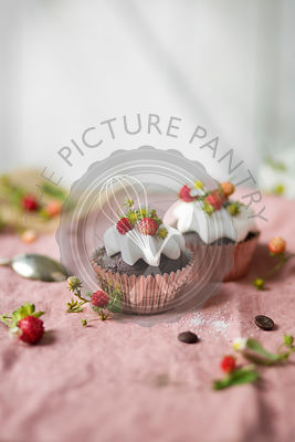Chocolate cupcake with whipped cream and wild strawberries on the table
