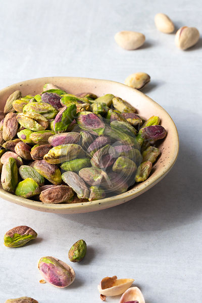 Roasted and salted pistachio nuts in a bowl.
