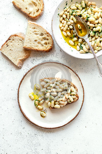 Creamy white bean salad with herb oil on a toast,top view
