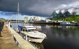A closeup of a yacht moored at Newcastle's Quayside on the river Tyne with the Baltic Art Museum, Gateshead Sage and Millenni...