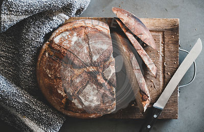 Freshly baked sourdough bread on wooden board over concrete background