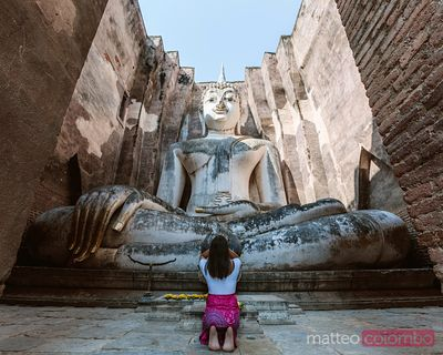 Woman praying in front of giant Buddha statue, Sukhothai, Thailand