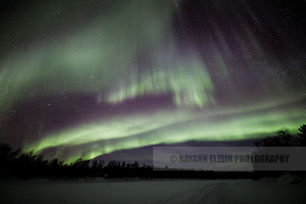 Northern lights above snowmobile tracks on the frozen Kaamanen river in northern Finnish Lapland
