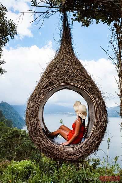 Woman inside a swing nest over lake, Munduk, Bali