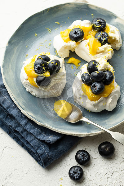 Meringues with lemon curd and blueberries on a hand-made plate, resting on a blue linen napkin. They are garnished with lemon...