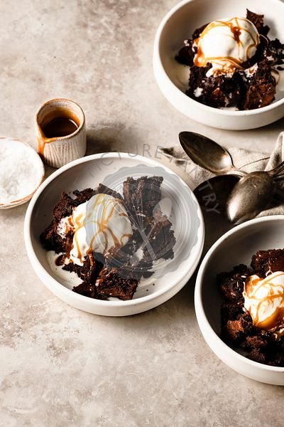 Bowls of buckwheat brownies with ice cream and caramel sauce.