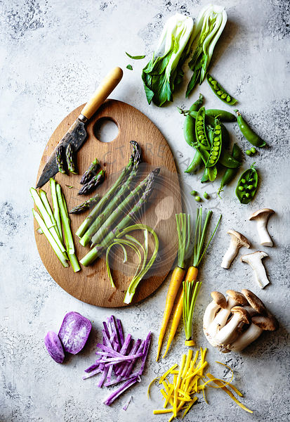 Sliced asparagus on a wooden cutting board with a selection of fresh colourful vegetables.