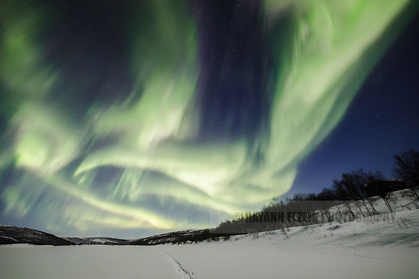 Very strong northern lights above the frozen Teno river in Utsjoki, Finnish Lapland