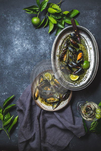 Mussels in green herb and white wine sauce with lemon on dark background.