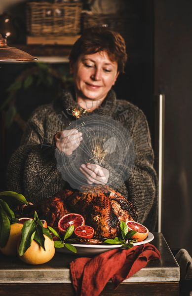 Smiling woman burning sparkles over Christmas dinner whole roasted turkey