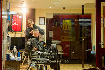 Barber Cutting Customer's Hair Through his Shop Window