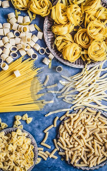 Dry pasta shapes on a blue background